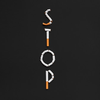 Vista elevada de la palabra parada hecha de cigarrillo sobre fondo negro