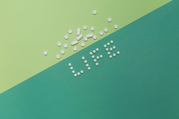 Vista elevada de la palabra de la vida con pastillas sobre fondo de color dual