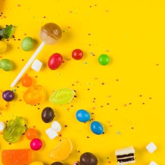 Vista elevada de paleta y caramelos sobre fondo amarillo