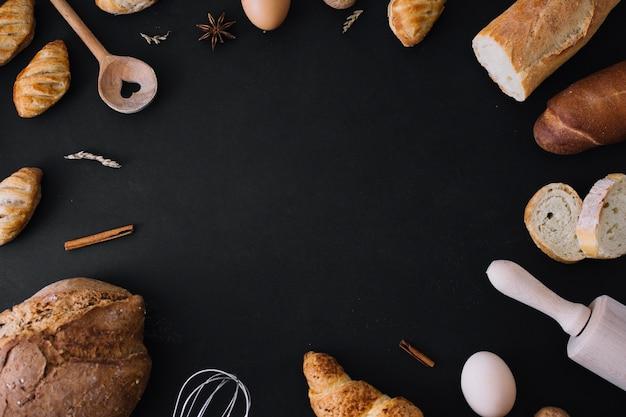 Vista elevada de panes; utensilios de cocina huevo y especias formando marco sobre fondo negro