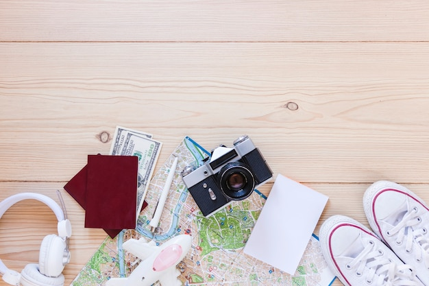 Vista elevada de papel blanco en blanco y accesorios de viajero en superficie de madera