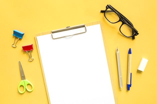 Vista elevada de papel blanco en blanco cerca de papelerías sobre fondo amarillo