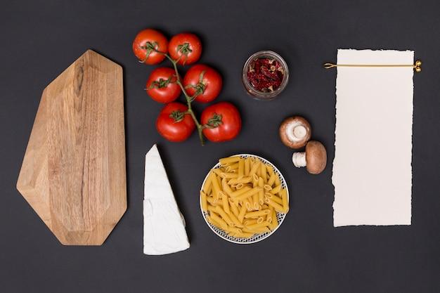 Vista elevada de papel blanco en blanco e ingredientes saludables para hacer sabrosas pastas