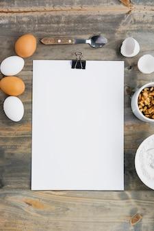 Vista elevada de papel en blanco con huevos y nueces sobre fondo de madera