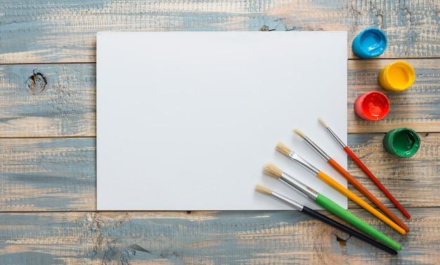 Vista elevada de papel blanco con pequeños contenedores de acuarela y pinceles en madera con textura