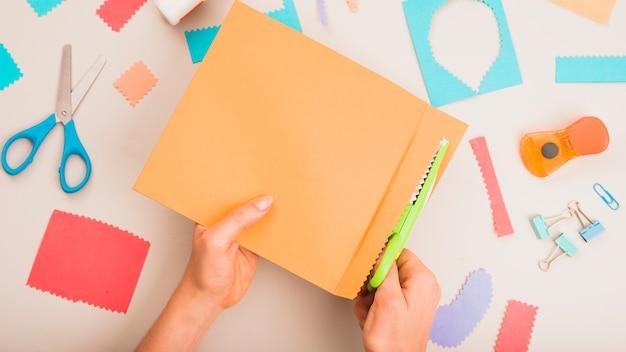 Vista elevada del papel de corte de la mano de la persona con tijera en zigzag con accesorios artesanales en mesa blanca