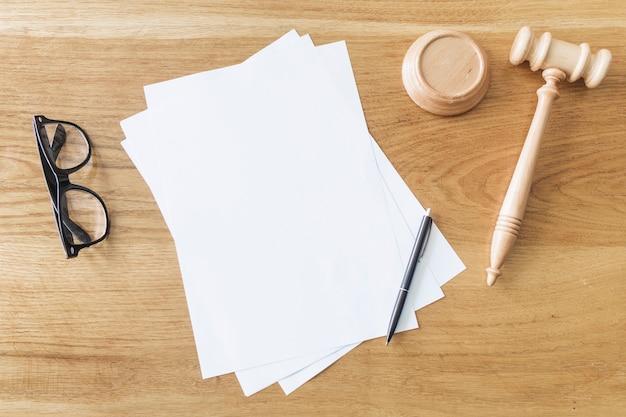 Vista elevada de papeles en blanco; gafas; pluma y mazo de madera en el escritorio en la sala del tribunal