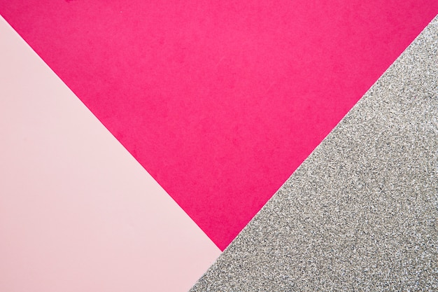 Vista elevada de papeles de cartón rosa y magenta en superficie gris