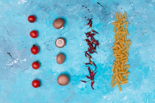 Vista elevada de la pasta cruda y el ingrediente dispuestos en fila sobre una superficie con textura azul