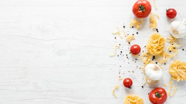 Vista elevada de pasta cruda de tallarines crudos con tomate; ajo y pimienta negra sobre tabla blanca.