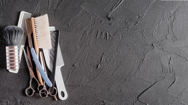 Vista elevada de peines, tijeras y maquinilla de afeitar en superficie negra