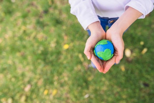 Vista elevada del pequeño globo de arcilla en manos ahuecadas sobre hierba