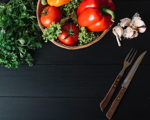 Vista elevada de perejil; pimiento; tomate; lechuga; dientes de ajo y utensilios para comer en superficie negra