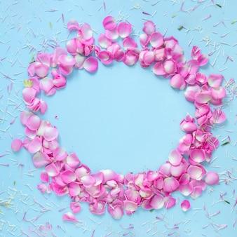 Vista elevada de pétalos de rosa que forman un marco circular sobre fondo azul