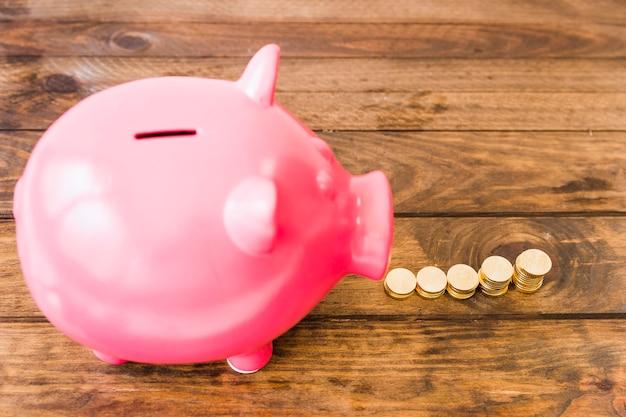 Vista elevada de piggybank rosa cerca de aumentar las monedas apiladas