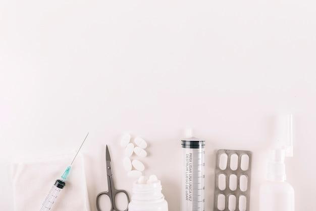 Vista elevada de píldoras y equipos médicos sobre fondo blanco