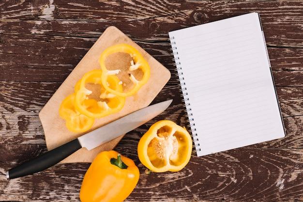 Una vista elevada de pimiento amarillo en tabla de cortar con cuchillo y cuaderno espiral en escritorio de madera