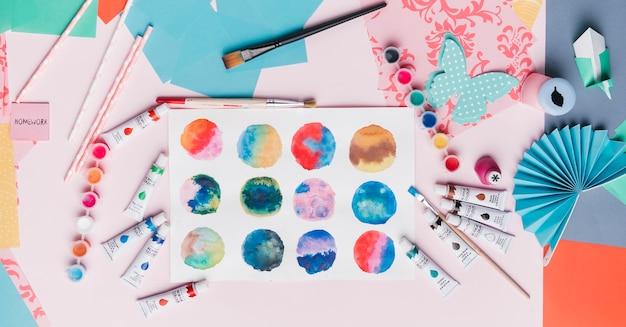 Vista elevada de la pintura abstracta colorida del círculo; paja; origami; y equipo de pintura