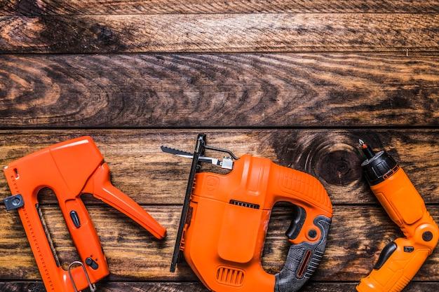 Vista elevada de la pistola de grapas, rompecabezas y taladro eléctrico sobre fondo de madera