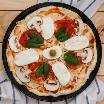 Una vista elevada de la pizza italiana con queso; albahaca; tomates y aceitunas en mesa de madera