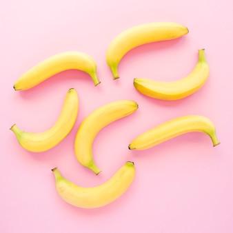 Una vista elevada de plátanos amarillos sobre fondo rosa