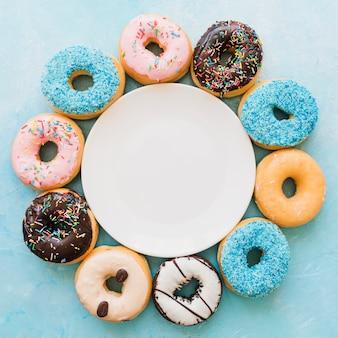 Vista elevada del plato rodeado de varios donuts frescos.