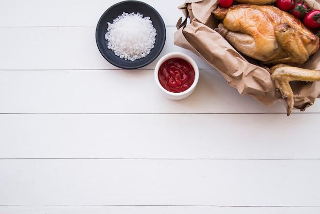 Vista elevada de pollo asado; salsa de tomate y sal en mesa de madera blanca