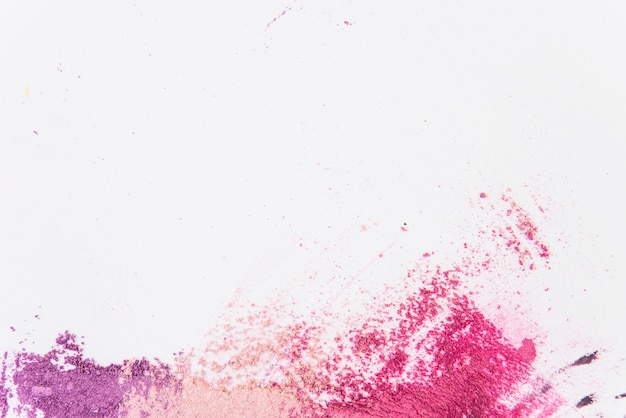 Vista elevada del polvo cosmético multicolor de la cara en el fondo blanco