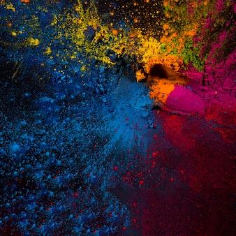 Vista elevada de polvos holi coloridos sobre fondo negro