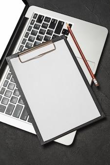 Vista elevada del portapapeles con papel en blanco y lápiz en el teclado del portátil