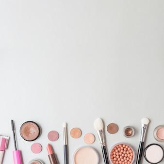 Vista elevada de productos cosméticos y pinceles sobre fondo blanco
