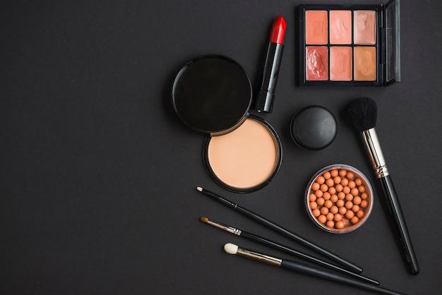 Vista elevada de productos cosméticos y pinceles sobre fondo negro