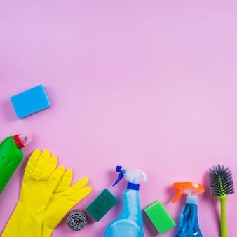 Vista elevada de productos de limpieza en fondo rosado