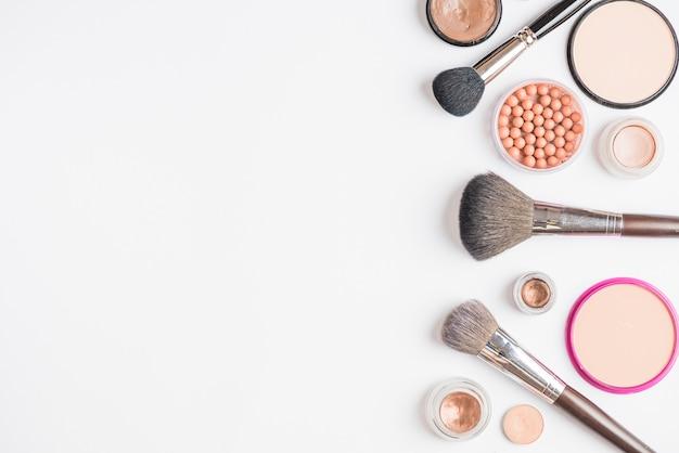 Vista elevada de productos de maquillaje sobre fondo blanco