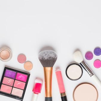 Vista elevada de productos de maquillaje sobre fondo blanco.