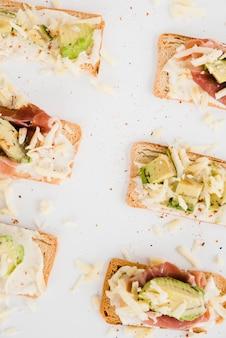 Una vista elevada de queso rallado y aguacate en rebanadas de pan