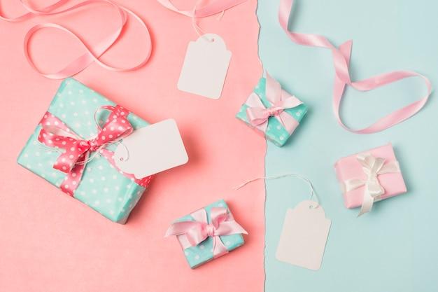 Vista elevada de regalos; etiquetas en blanco y cinta