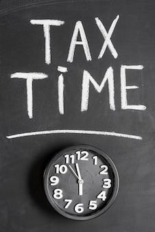 Vista elevada del reloj de alarma con texto de impuesto sobre el tiempo en superficie negra