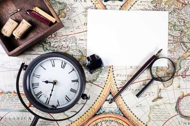 Vista elevada del reloj, papel, pluma y botella de tinta en el mapa