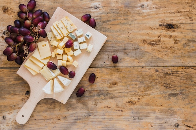 Una vista elevada de rodajas de queso fresco y cubos con uvas rojas en mesa de madera