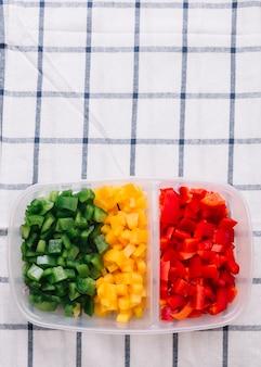 Una vista elevada de rojo picado; pimiento verde y amarillo en el recipiente de plástico sobre el mantel a cuadros