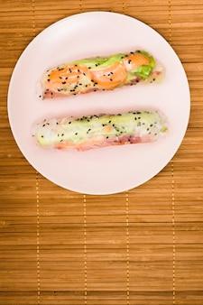 Vista elevada de los rollitos de primavera asiáticos con salmón pescado y verduras en un plato blanco sobre mantel
