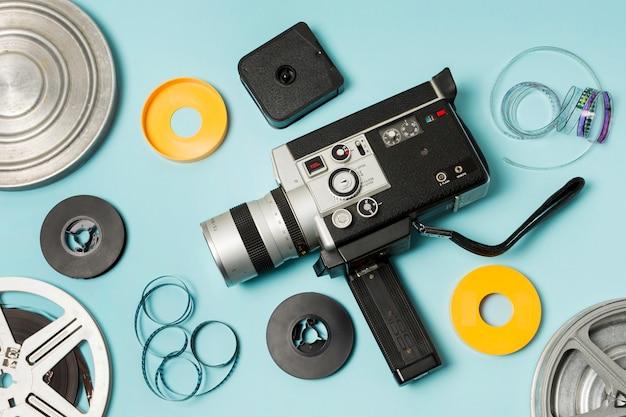 Una vista elevada del rollo de película; tiras de película y videocámara sobre fondo azul