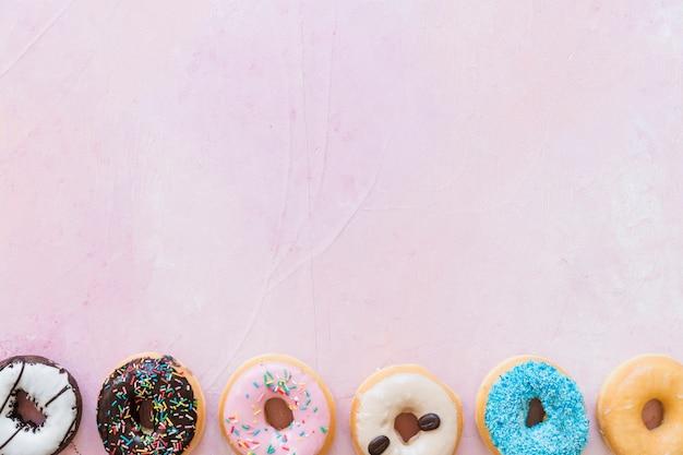Vista elevada de rosquillas frescas en una fila sobre fondo rosa