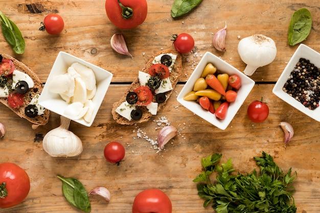 Vista elevada de sabrosa bruschetta e ingredientes frescos italianos sobre la mesa