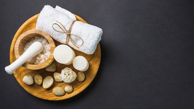 Vista elevada de la sal; toalla; velas y piedras de spa en placa de madera sobre fondo negro
