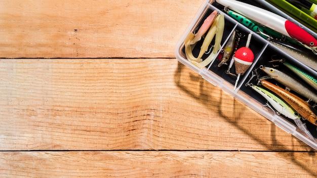 Vista elevada de señuelos de pesca y flotadores de pesca en el contenedor en mesa de madera