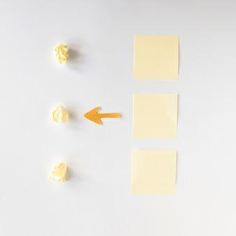 Vista elevada del símbolo de flecha entre papeles arrugados y notas adhesivas