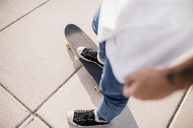 Vista elevada del skater de pie en el tablero largo