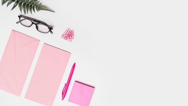 Vista elevada del sobre; bolígrafo; nota adhesiva helecho artificial gafas y clips de papel sobre superficie blanca.